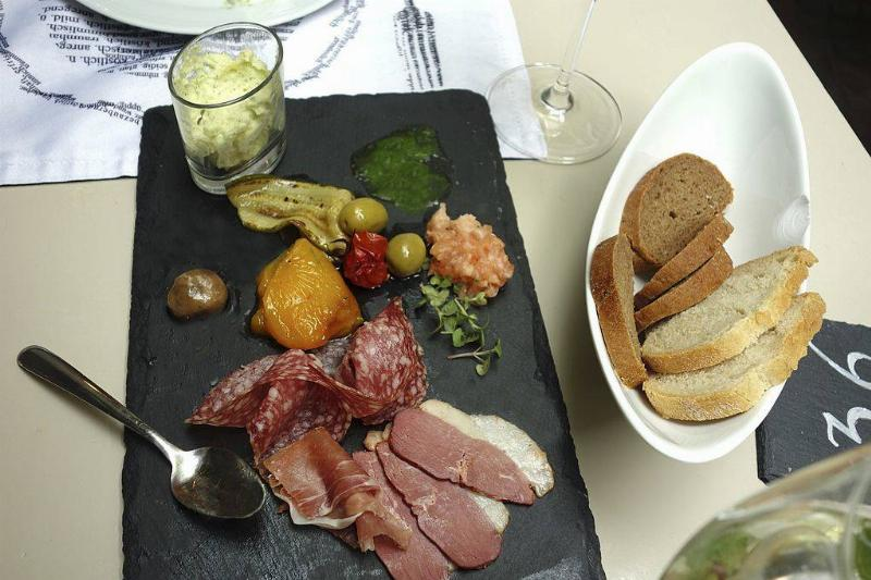 a platter of meat, olives, and sauces with some bread