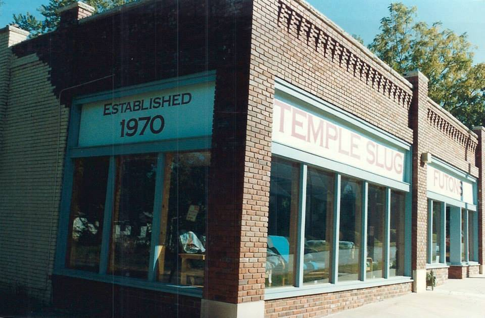 the exterior of a brick building that reads established 1970, temple slug, futons