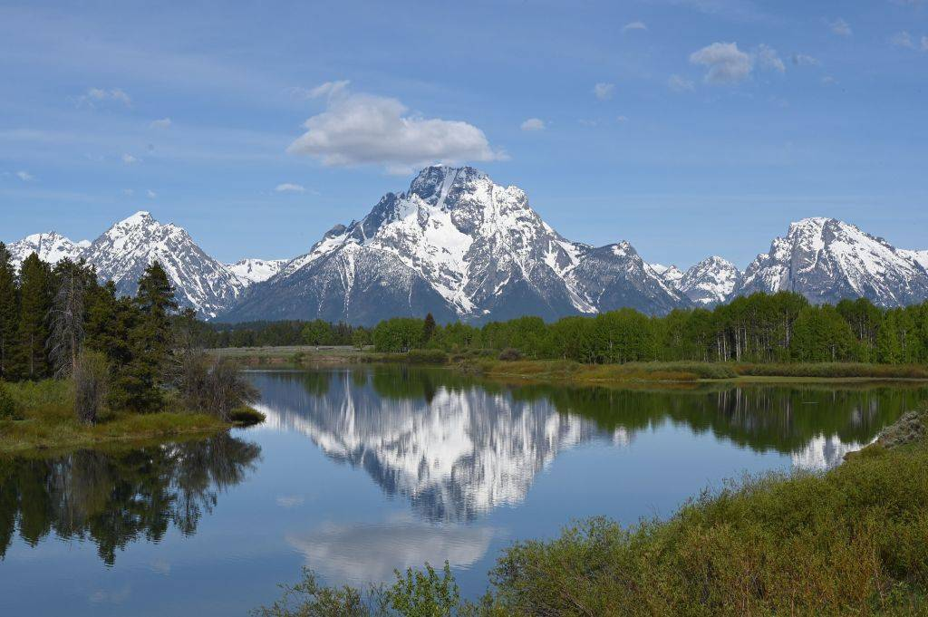 a lake in front of the mountains at Grand Teton National Park in Wyoming