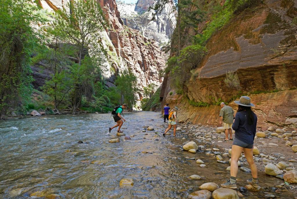 backpackers stepping across stones in the water at zion national park