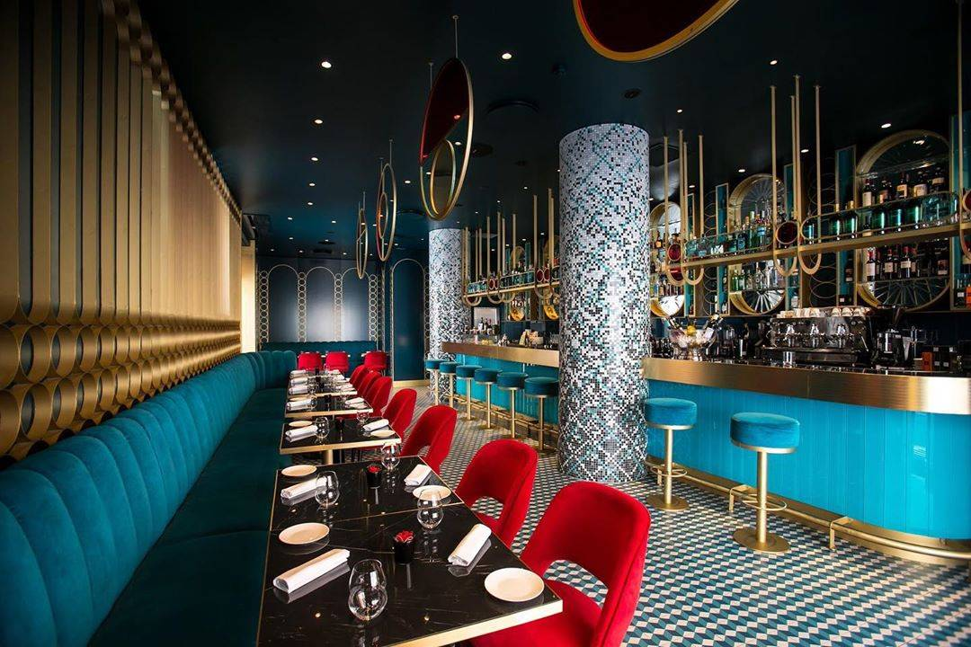 restaurant interior features red and blue velvet seating and gold accents