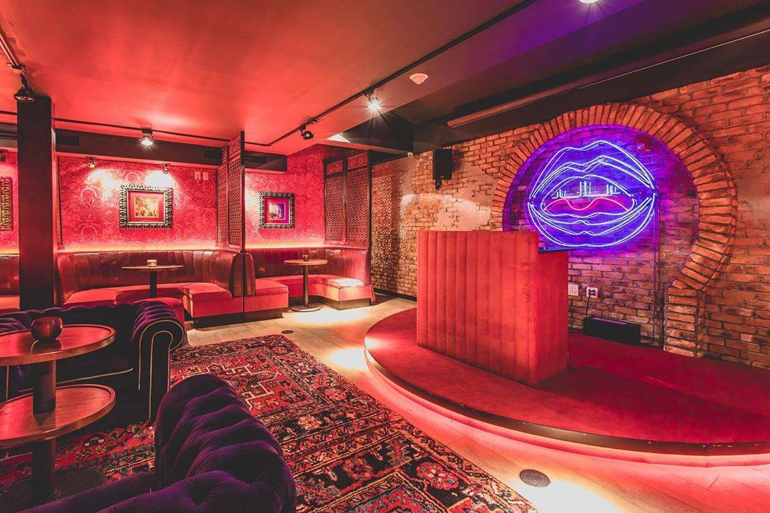 luxurious rugs, pink lighting, and lip-shaped neon lights