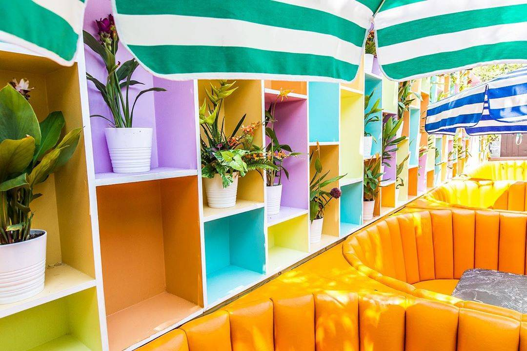 brightly colored booths and decor with plants everywhere