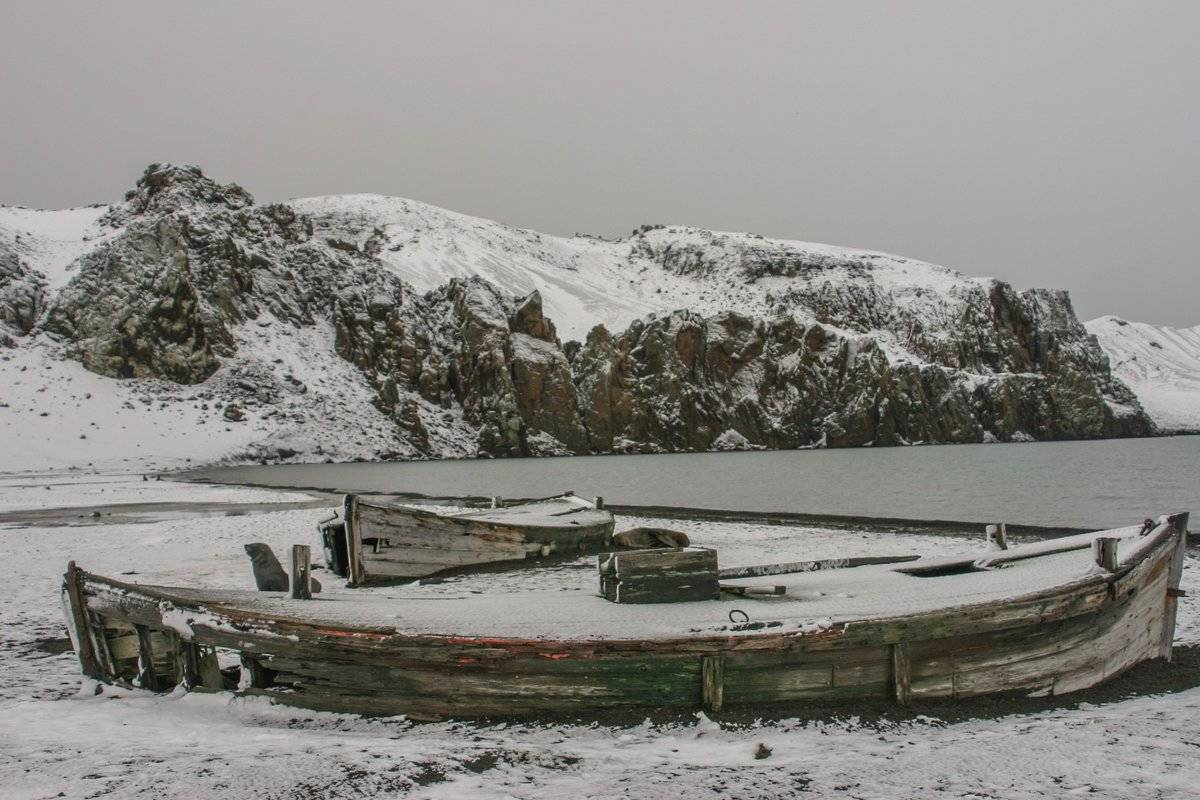 Abandoned boats sit on the snowy shore of Bouvet Island.