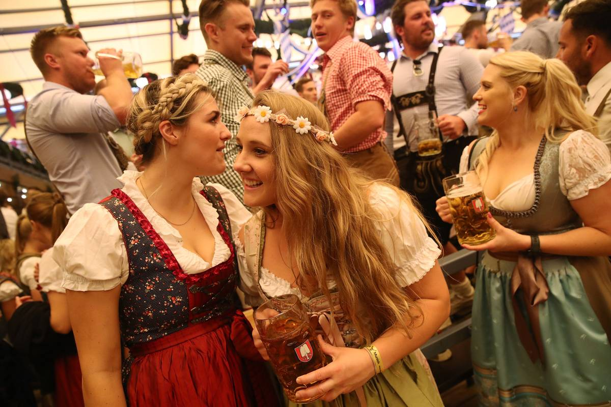 Revelers, including three young women from Australia, celebrate in the Schottemhamel tent on the opening day of the 2018 Oktoberfest