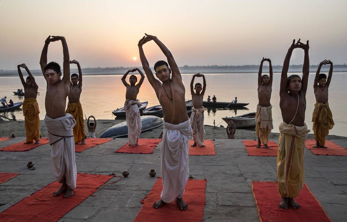 Young Indian Hindu Brahmins training to be priests perform yoga on a ghat on the Ganges River