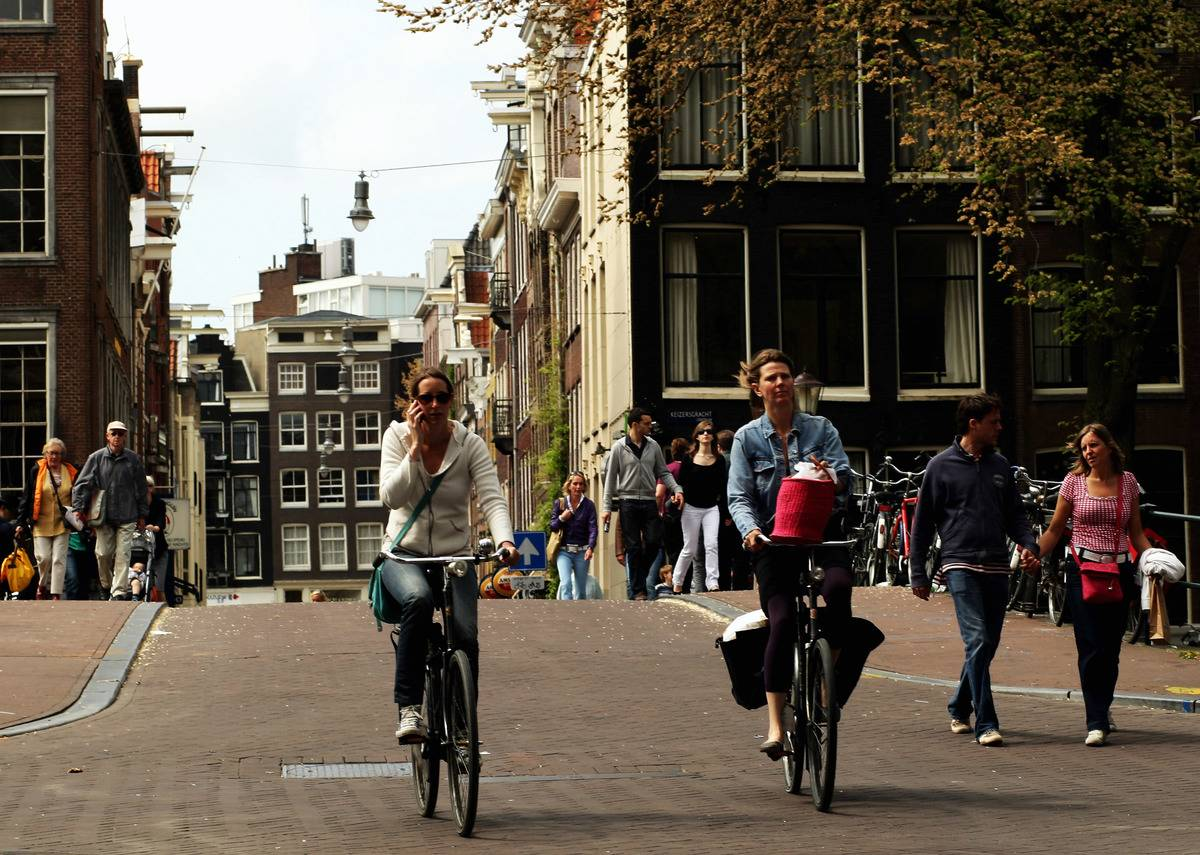 Cyclists make their way through the city streets of Amsterdam