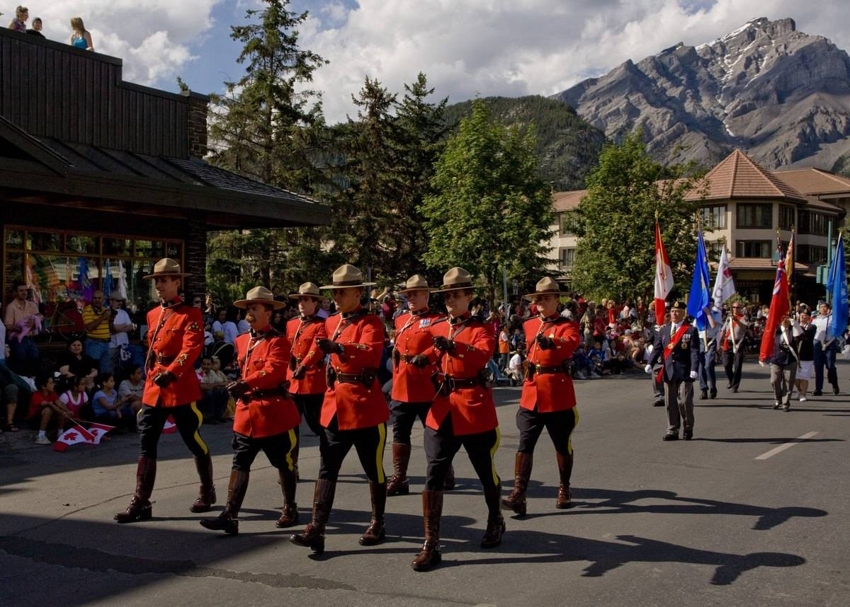 group of Royal Canadian Mounted Police march down Banff Avenue