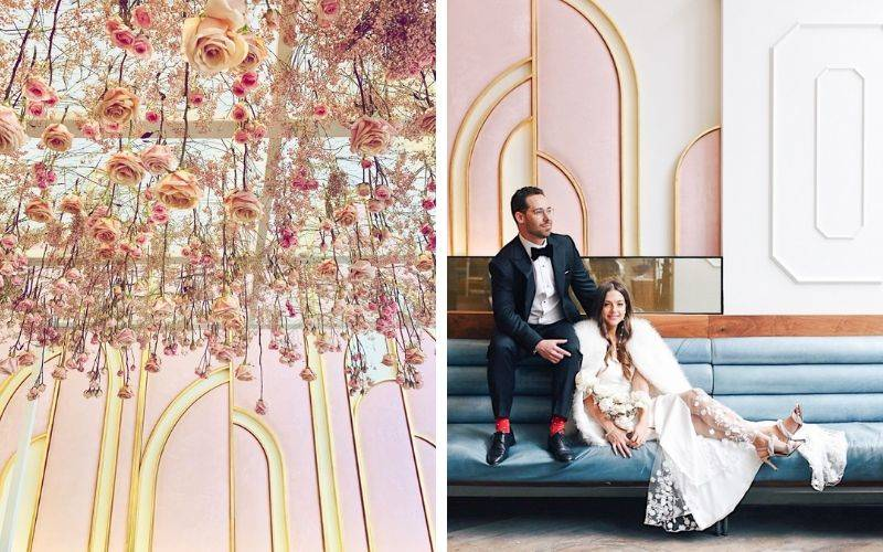 flowers haning from ceiling and pink decor on walls behind groom and wife sitting on blue seats