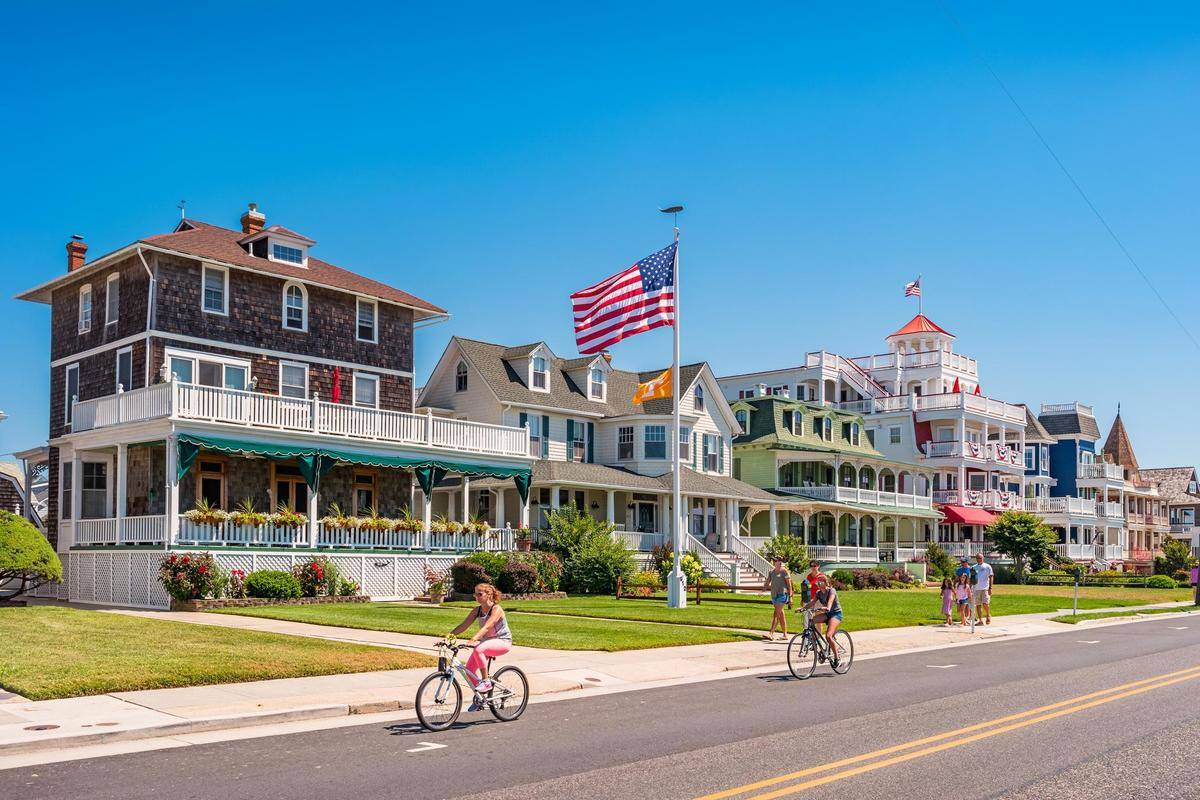 people riding bikes in front of houses in Cape May, New Jersey
