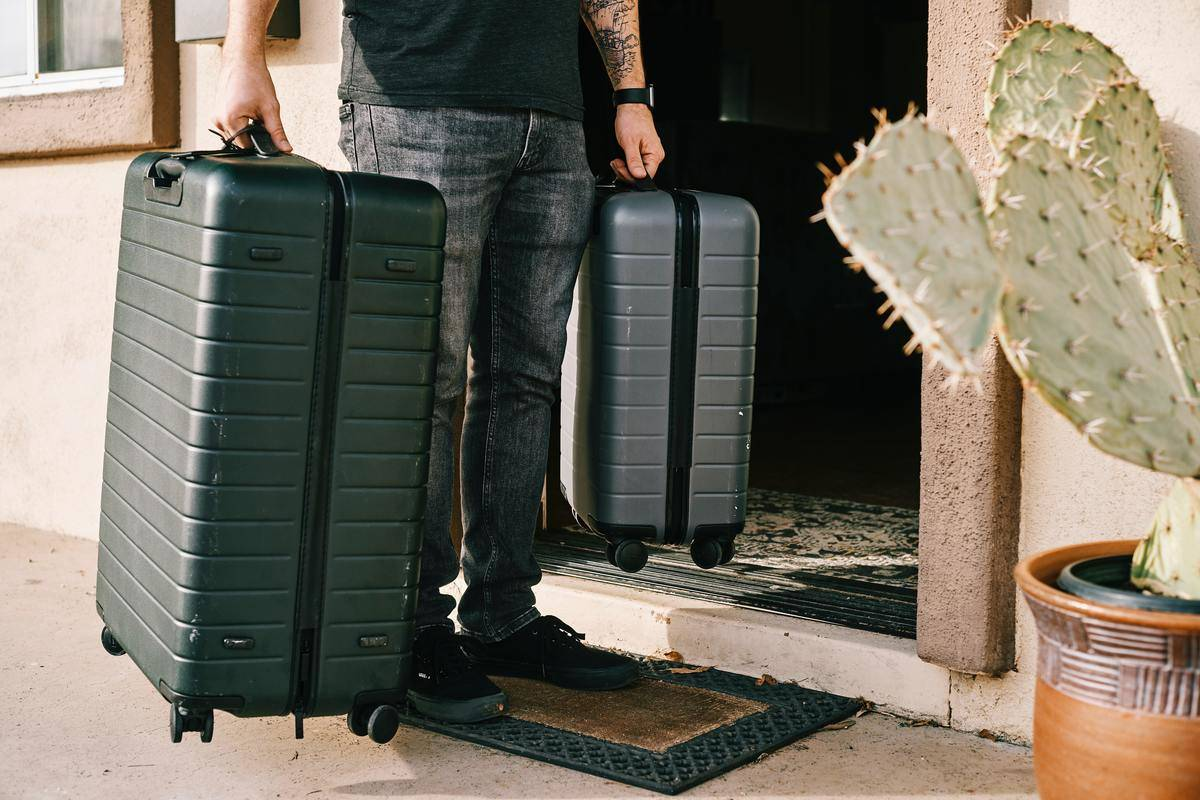 man carrying two packed suitcases one smaller