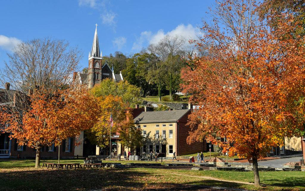 the historic district with a church and colorful trees in Harpers Ferry, West Virginia