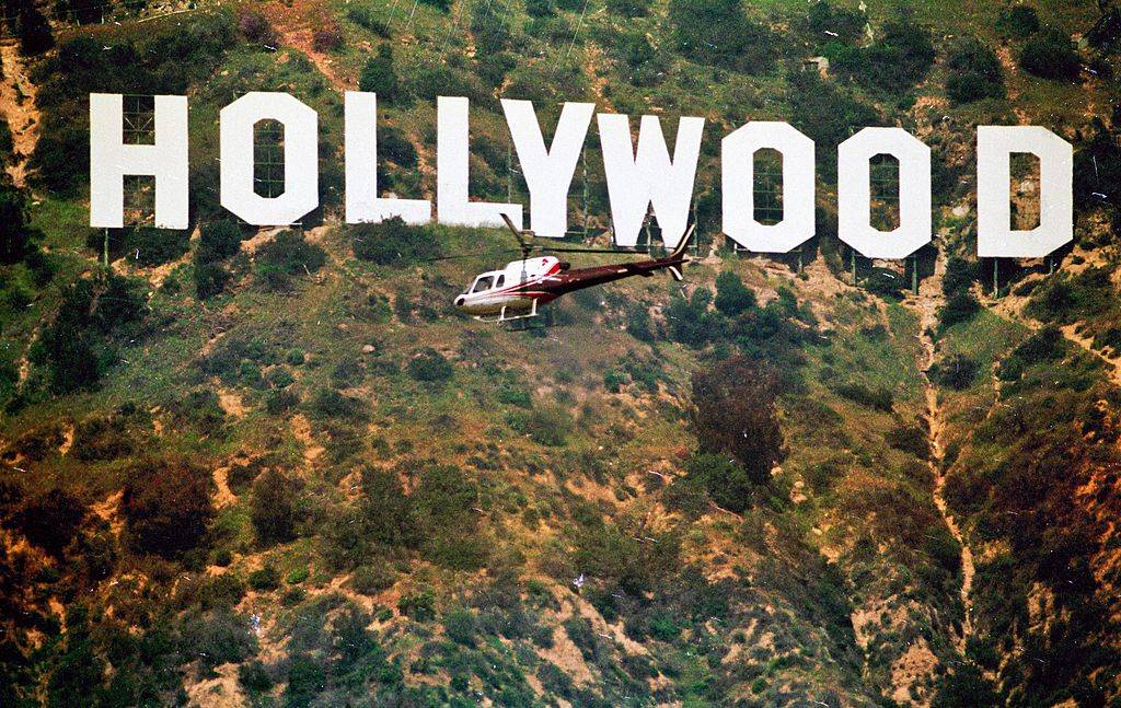 a helicopter flying in front of the hollywood sign