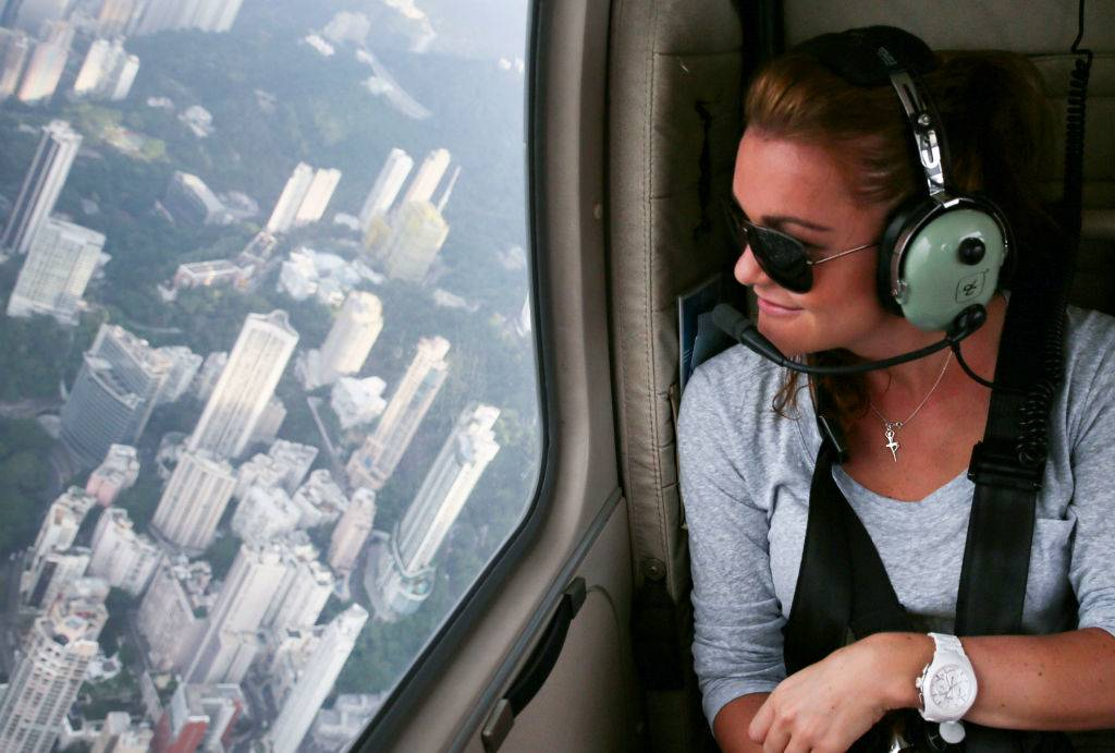 a girl flying in a helicopter over the skyscrapers in hong kong