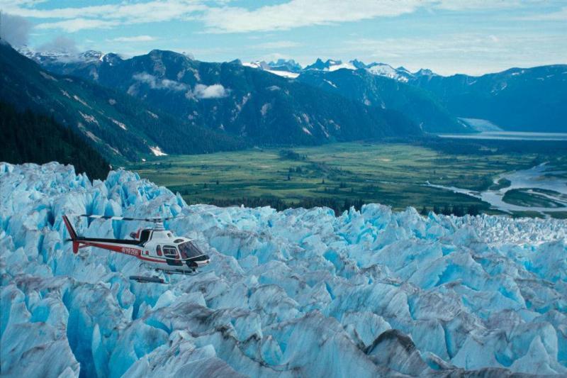 a helicopter flying over a glacier in juneau, alaska