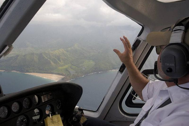 a helicopter pilot looking out onto the green mountains and ocean in kauai from his helicopter