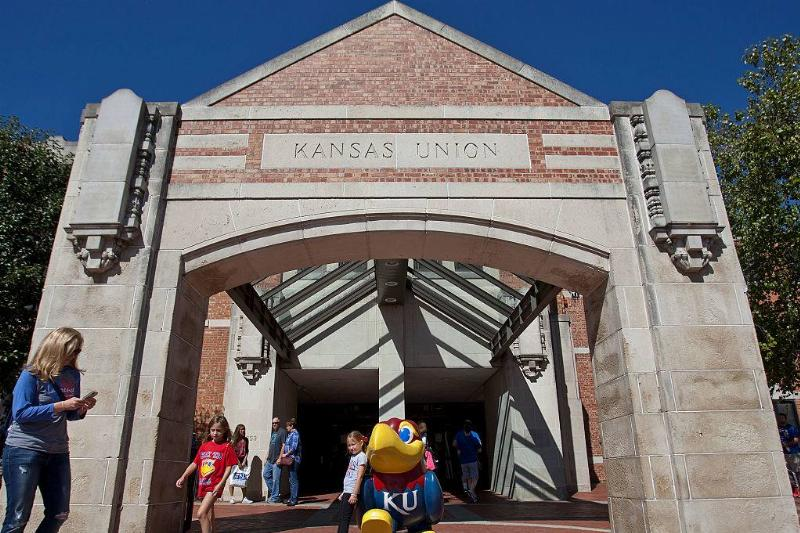 a girl posing with a statue of the bird mascot at university of kansas in Lawrence, Kansas