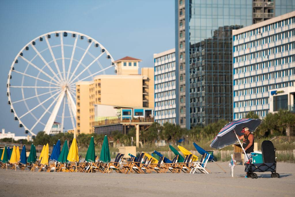 a man putting up an umbrella on a beach with buildings and a ferris wheel in the background in Myrtle Beach, South Carolina