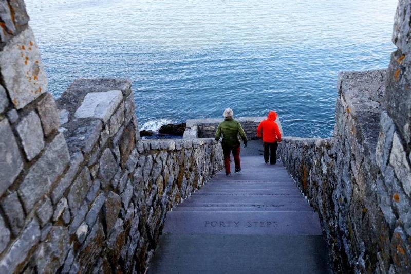 people walking down steps near the ocean in Newport, Rhode Island
