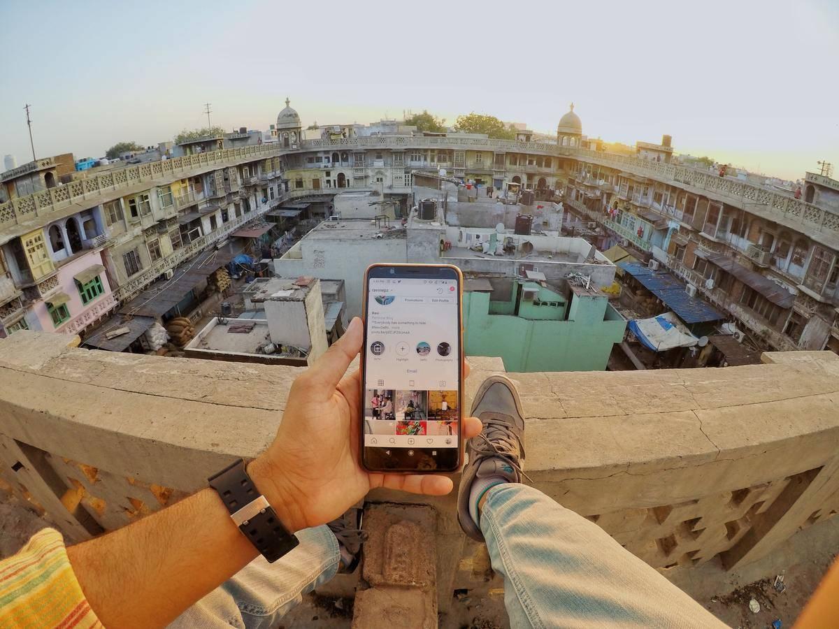 man using phone on ledge of city