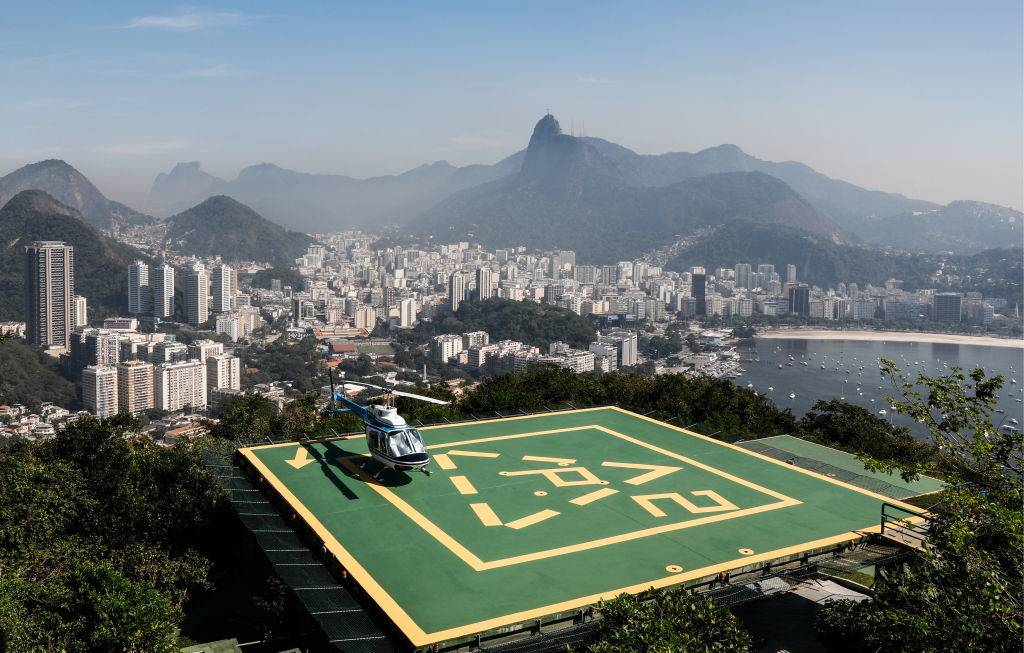 a helicopter on a launch pad atop the hills of rio de janeiro