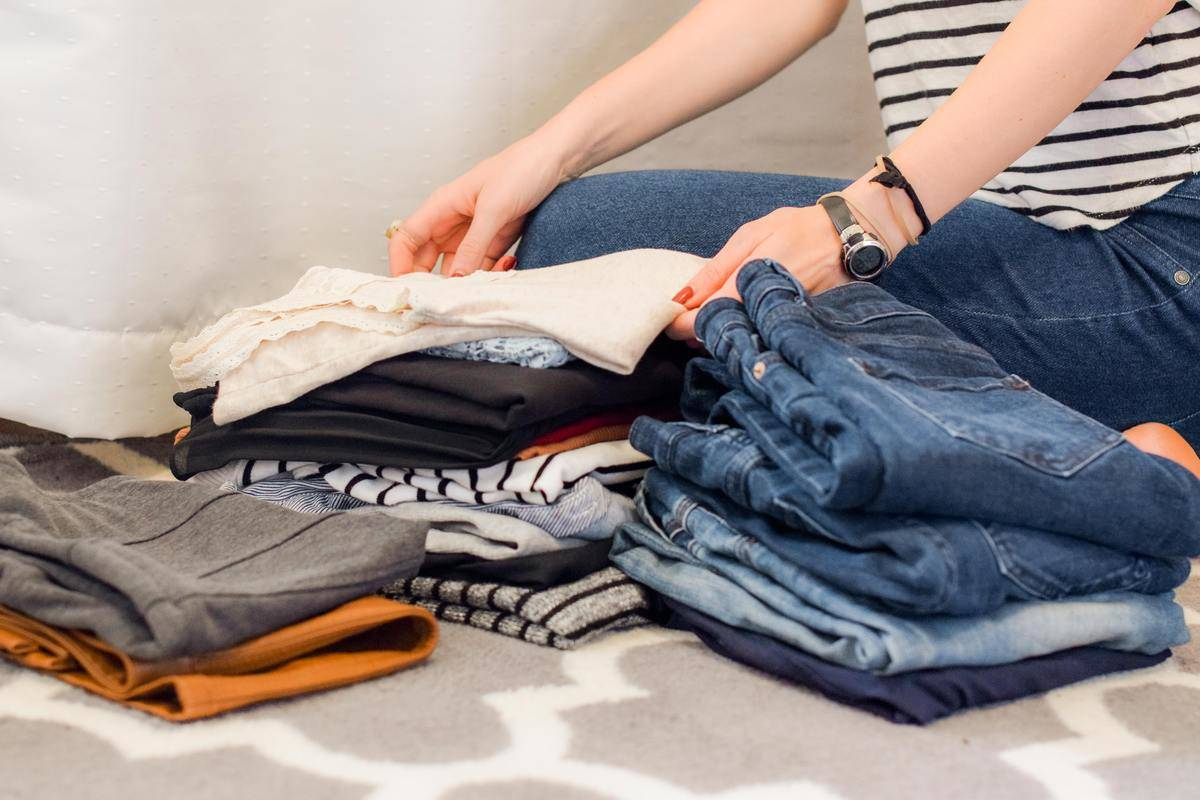person folding piles of clothes