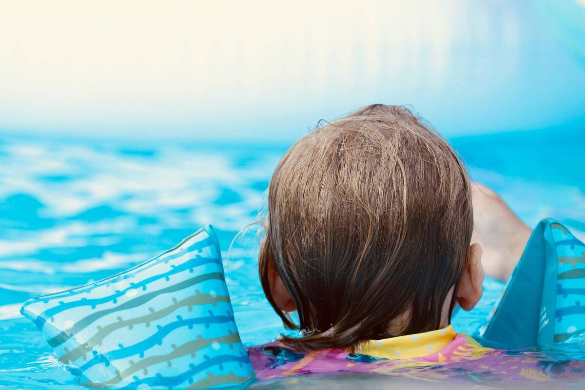 child swimming water wings