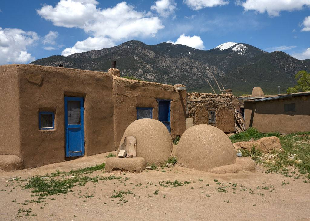 traditional adobe bread ovens in front of a pueblo in Taos, New Mexico
