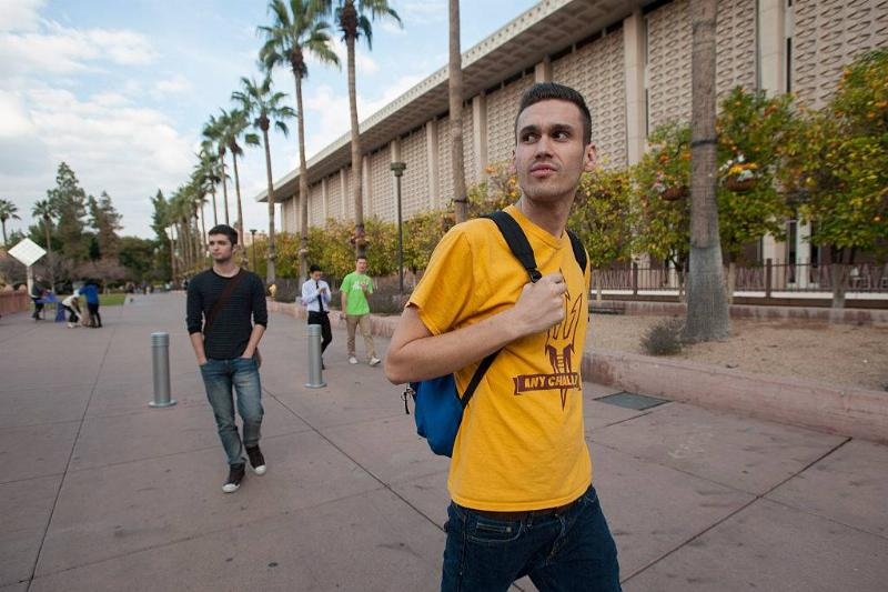 a male student walking around with a backpack at Arizona State University in Tempe, Arizona