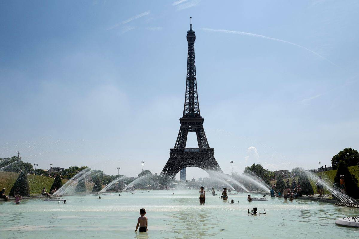 People cool themselves at the Trocadero Fountain in front of The Eiffel Tower in Paris