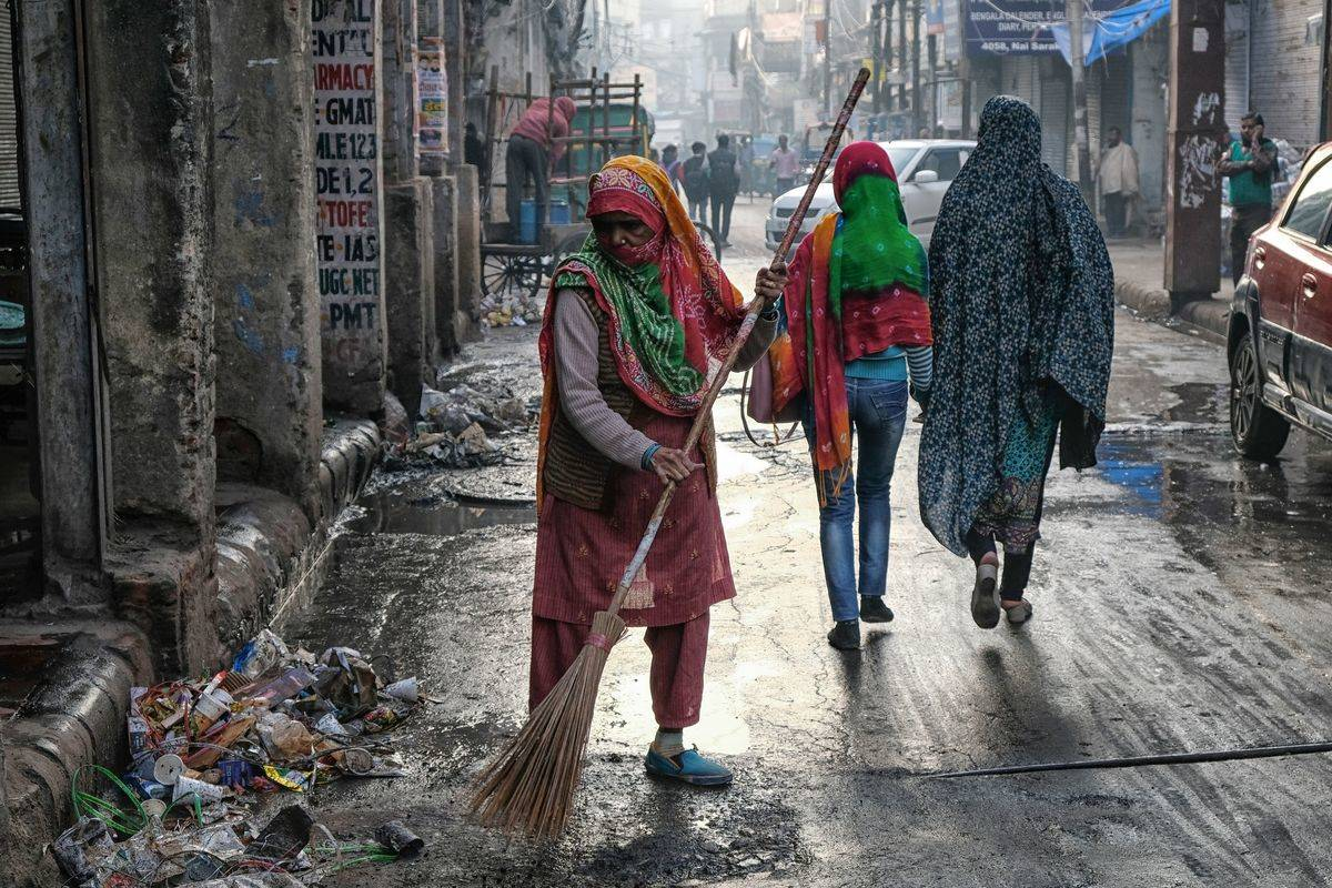 street sweeper cleaning up garbage in new delhi
