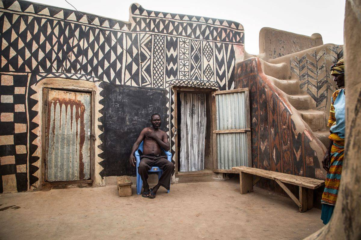 An man sits in the courtyard of his house in the notable village of Tieble's royal court