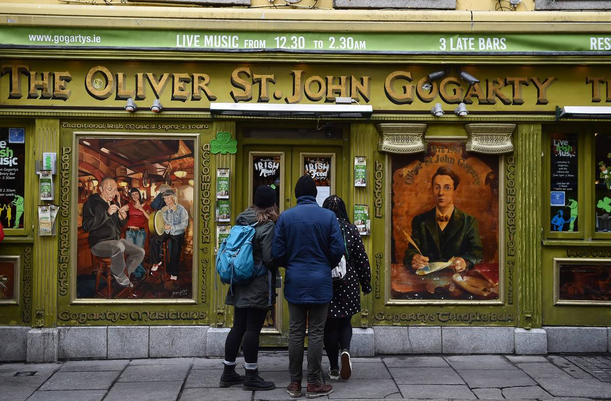 Tourists check to see if a bar in the Temple Bar district is open