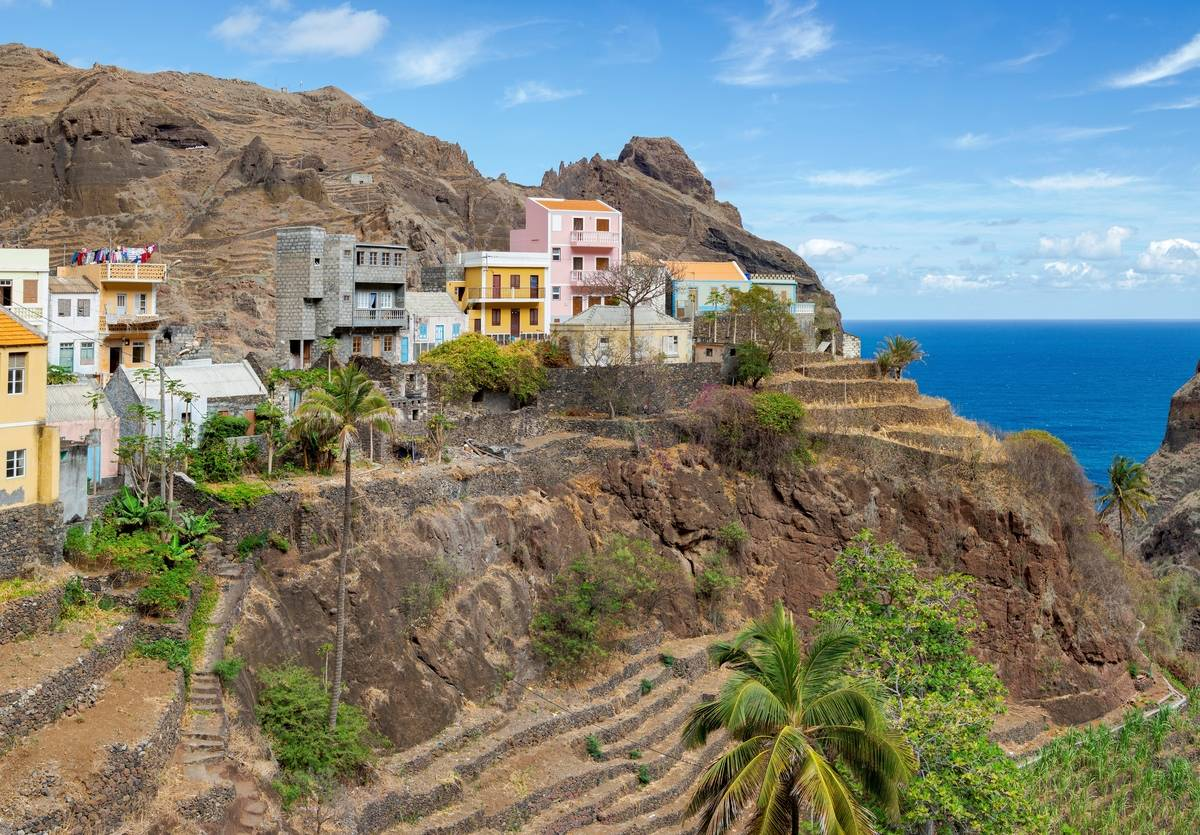 colorful houses on cliff edge with blue water in background