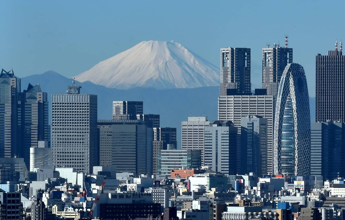 Japan's highest mountain, Mount Fuji (C) is seen behind the skyline of the Shinjuku area of Tokyo