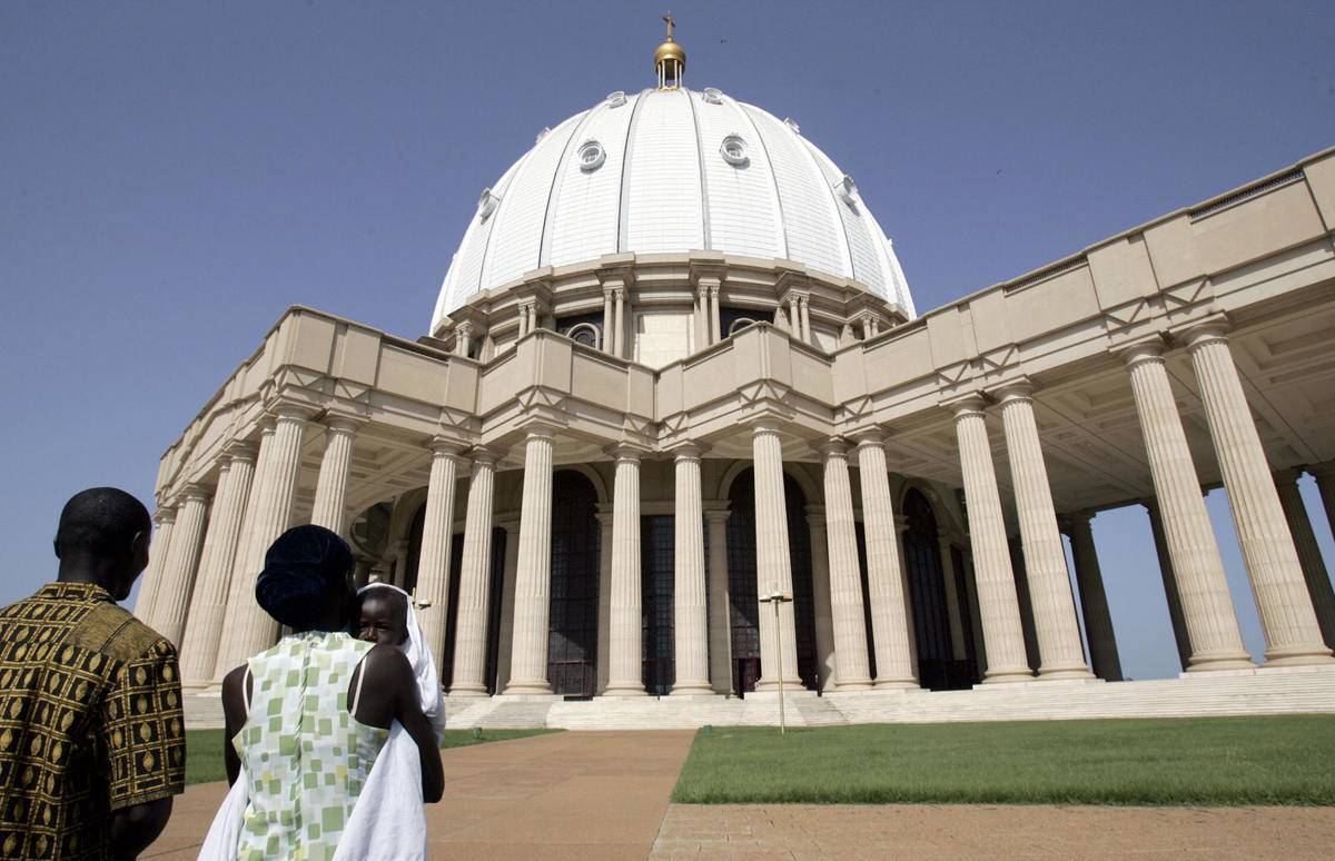 An Ivorian couple and their baby arrive for a mass in Yamoussoukro's