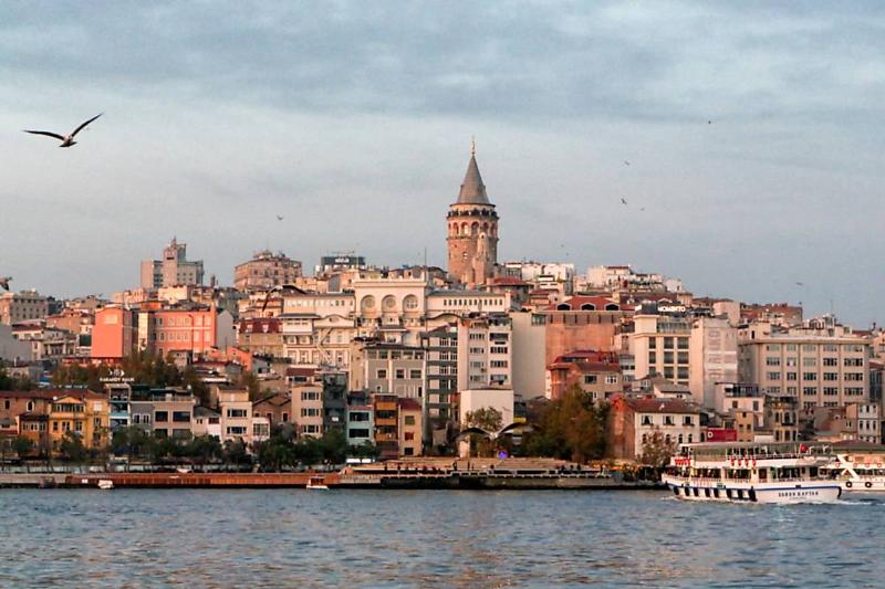Landscape photograph of the Istanbul waterfront and Bosphorus Strait in the early morning, with the city skyline visible in the background,