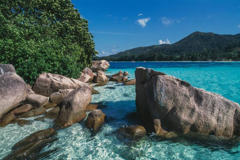 Granite boulders and crystal clear sea in an islet in front of Praslin island, Seychelles.