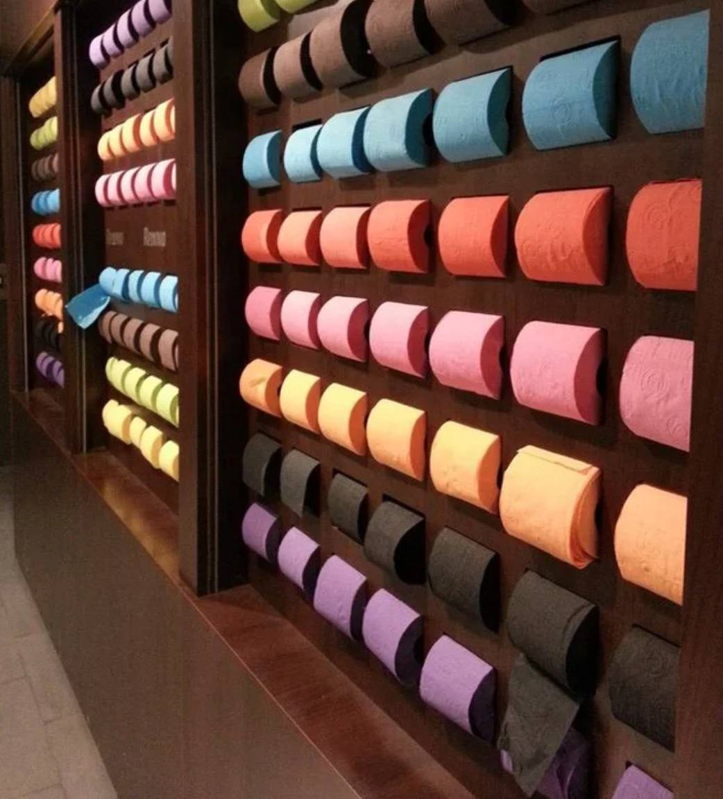 rows of different colored toilet paper rolls displayed on wall