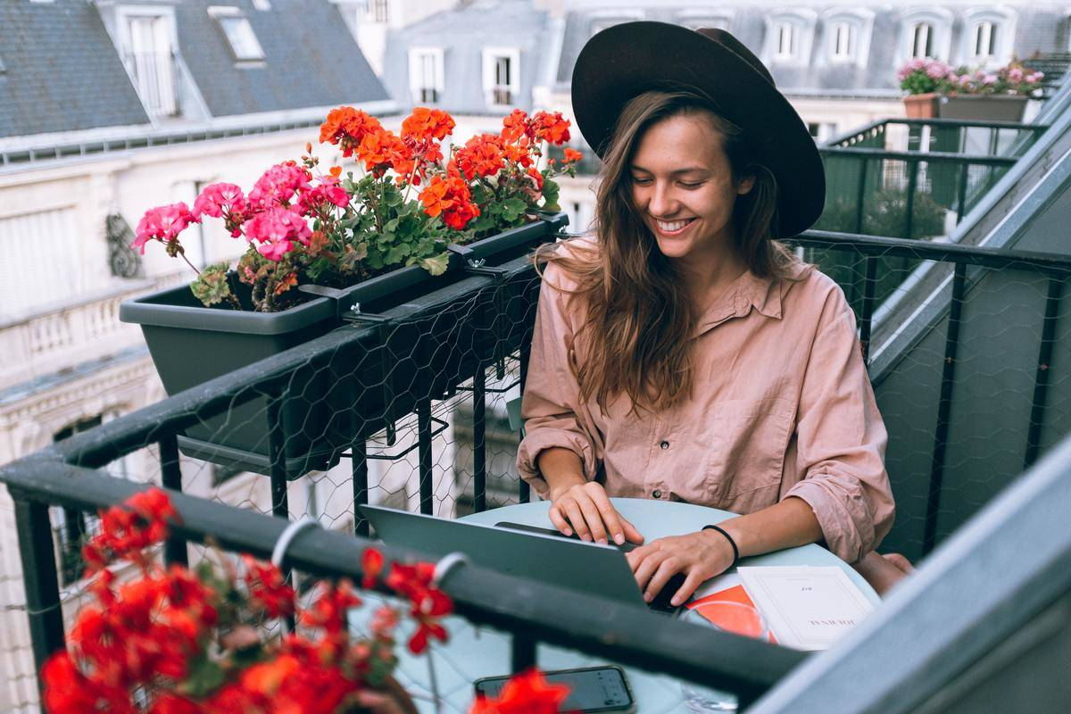 woman in france on balcony working at laptop