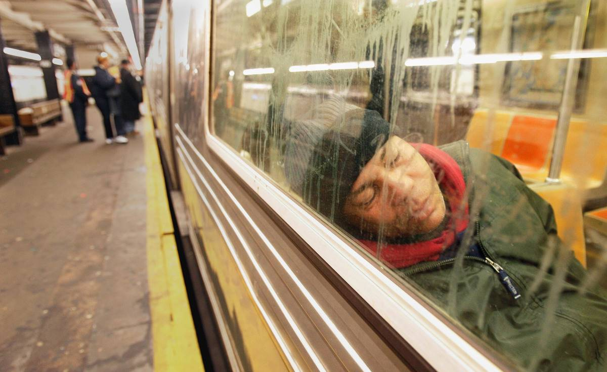 A man sleeps on the subway in the early morning hours