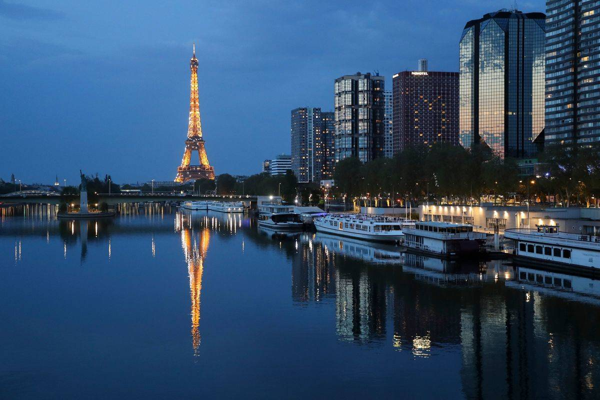 General view of the illuminated Eiffel Tower reflected on the Seine river in Paris at night