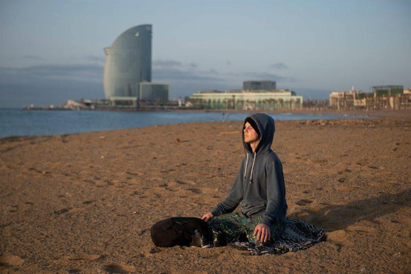A man meditates as he parctices yoga at dawn at La Barceloneta Beach