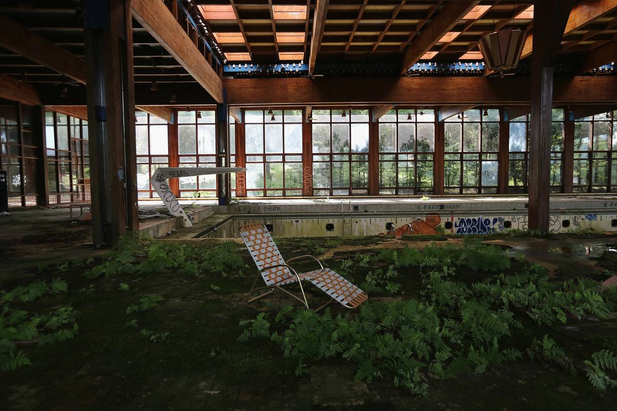 A lawn chair sits as nature takes over the indoor pool area of Grossinger's Catskill Resort Hotel