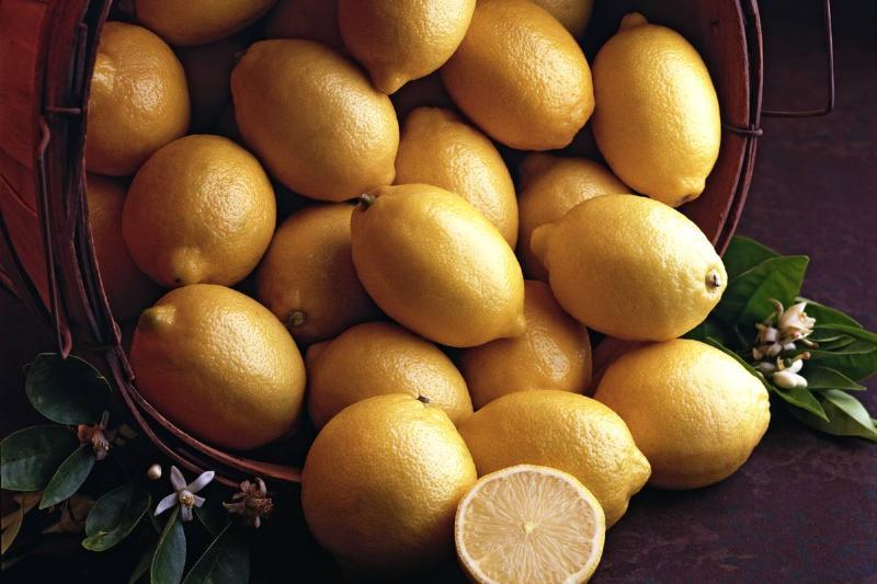 View of a basket of lemons, with one lemon cut in half