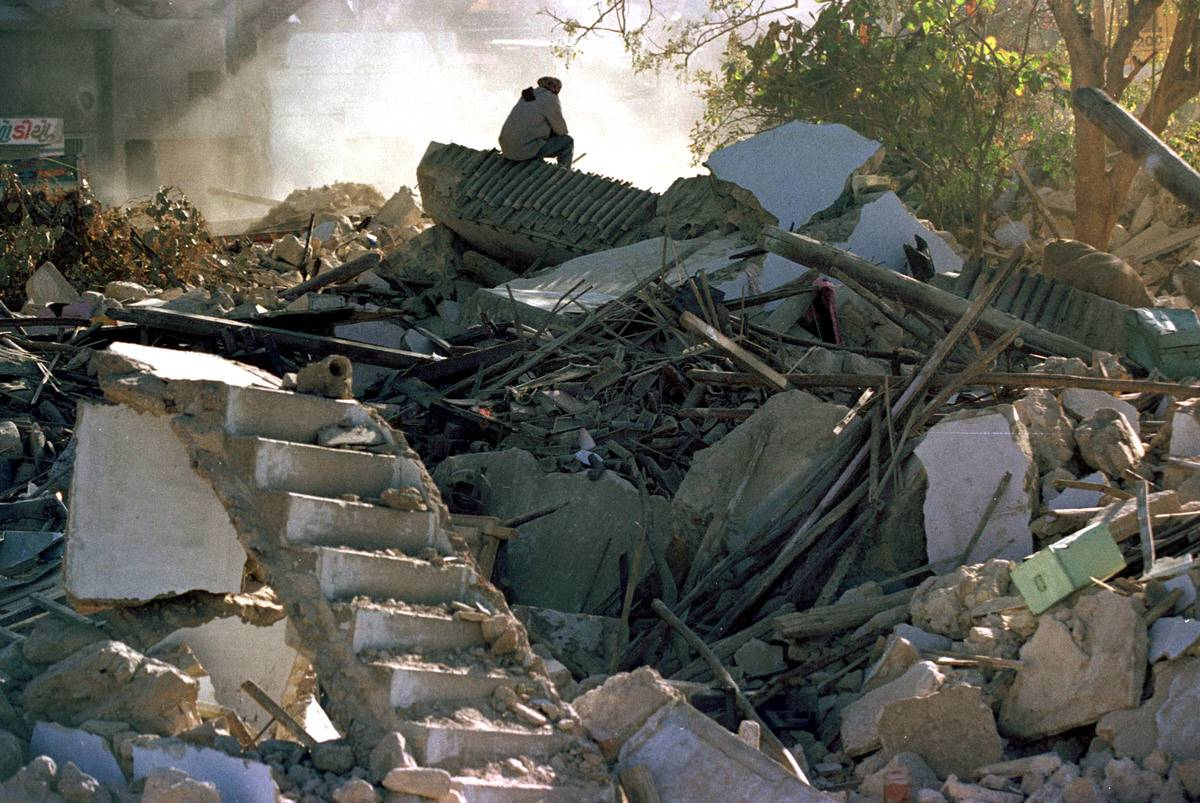 A man sits on top of what used to be his home while watching bulldozers clear the ruins of Old Anjar