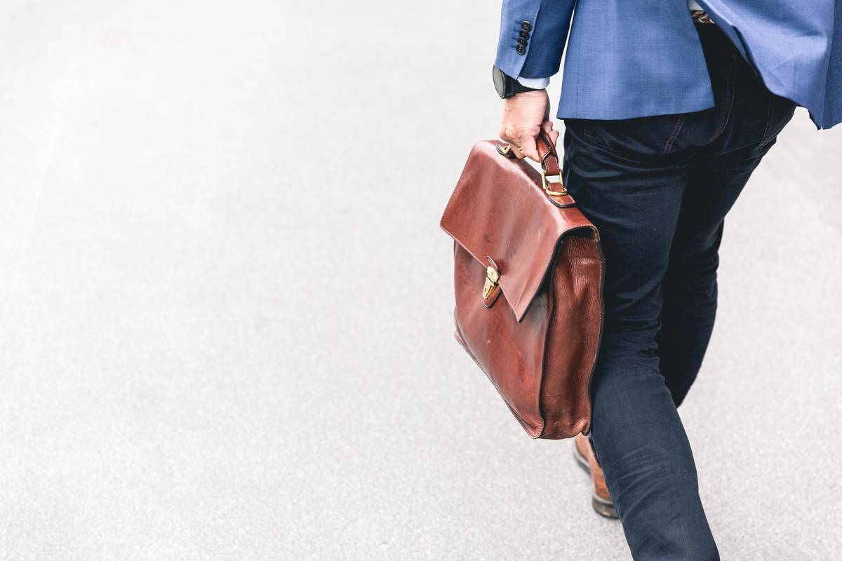man holding briefcase on the way to work