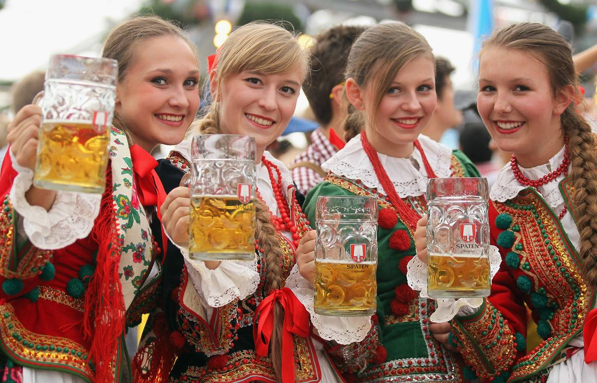 Women dressed in traditional costume enjoy drinking beer after participating in the opening parade during day 2 of Oktoberfest beer festival