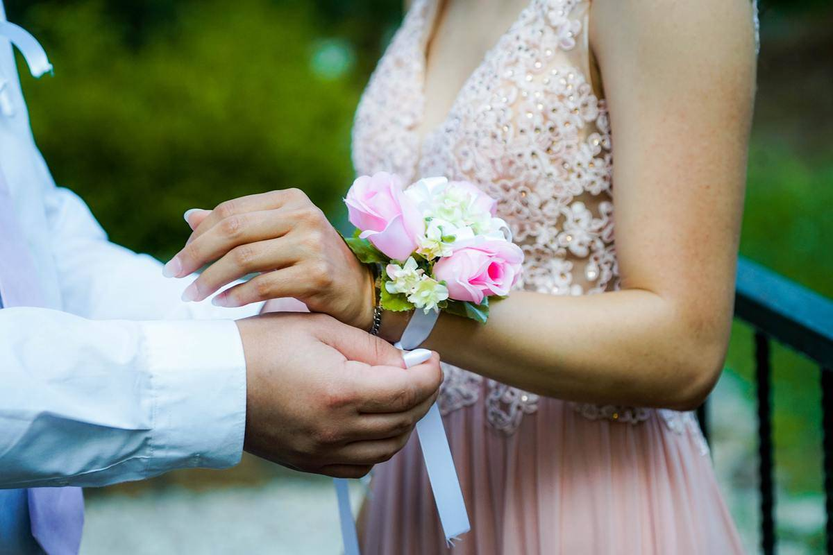 boy places on corsage on prom date