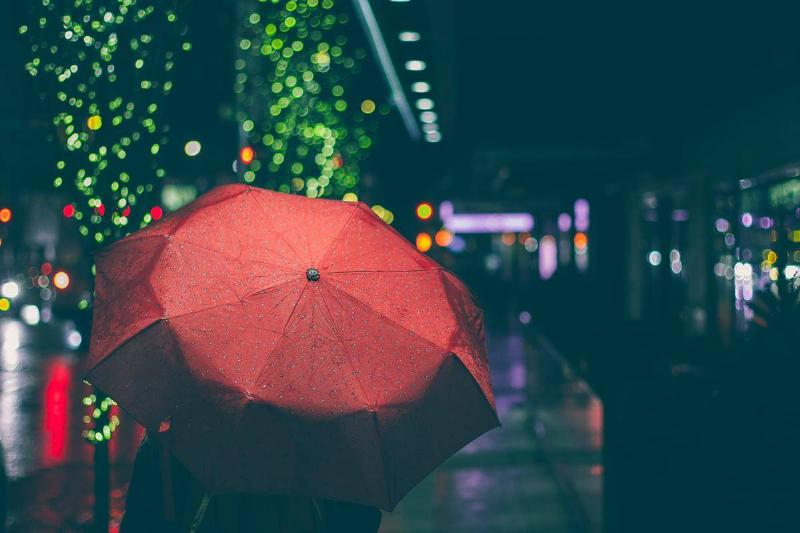 Person holds red umbrella in the city